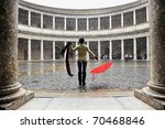Snowing over woman with red umbrella in palace - stock photo