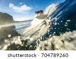 muscular surfer riding on big... | Shutterstock . vector #704789260