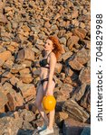 Small photo of Red ore. Mountains of red ore. A girl in a swimsuit lies on a red ore