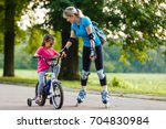 a young mother roller skating.... | Shutterstock . vector #704830984