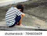 a sad boy is sitting on the... | Shutterstock . vector #704833609