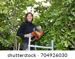 woman trimming her hedge in the ... | Shutterstock . vector #704926030