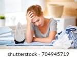 a tired woman housewife ironing ... | Shutterstock . vector #704945719