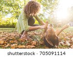 Small photo of Adult woman playing with a dogs at park or in the backyard. Autumn colors, unstaged situation with candid model and playful dogs. Lifestyle and friendship concepts.