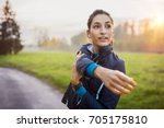 woman stretching at park while... | Shutterstock . vector #705175810