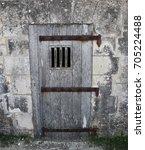 wooden door of a prison cell | Shutterstock . vector #705224488