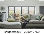 senior couple are cuddled up on ... | Shutterstock . vector #705249760
