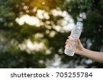 hand holding water bottle in... | Shutterstock . vector #705255784