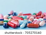 Small photo of Heap of various pills on color background