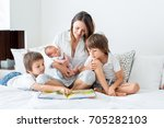 young mother  read a book to... | Shutterstock . vector #705282103