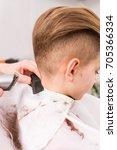 little boy getting haircut by... | Shutterstock . vector #705366334