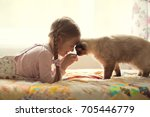 Stock photo pretty girl plays with a cat 705446779