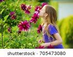 adorable little girl sniffing... | Shutterstock . vector #705473080