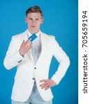 Small photo of Businessman posing in white jacket, shirt and pants. Man holding business or bank card. Banking and saving. Manager wearing casual suit on blue background. Fashion and information concept.
