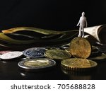 Small photo of man figurine standing on an instable coin having banknotes as background