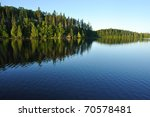 Reflections on the Coniferous Forest on a Wilderness Lake - stock photo