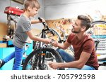 dad and son fixing bicycles in... | Shutterstock . vector #705792598