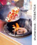 tossing vegetables in a wok.... | Shutterstock . vector #705847414