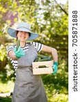Small photo of Brunette agronomist in with cucumbers box