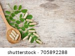 herbal capsules on moringa leaf ... | Shutterstock . vector #705892288