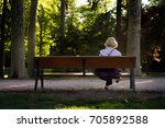Old Lady Reading On A Bench In...