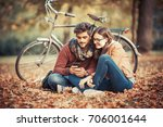 young couple sitting outdoors... | Shutterstock . vector #706001644