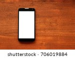Small photo of Mockup image of b;acl mobile phone with blank white screen on dark wooden table