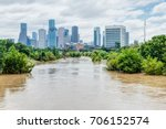 Small photo of High and fast water rising in Bayou River with downtown Houston in background under cloud blue sky. Heavy rains from Harvey Tropical Hurricane storm caused many flooded areas in greater Houston area.