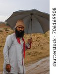 Small photo of RAJASTHAN, INDIA - MARCH 10, 2006: Man with beard and umbrella on the roads protecting from monsoon rain