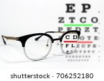 Small photo of Reading glasses with vision acuity chart exam on white background