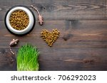 Stock photo bowl full and overflowing with dry pet cat food bits and mouse toys on wooden background top view 706292023