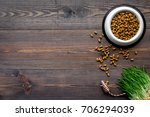 Stock photo pet care with dry food for pet cat in plastic bowl on wooden background top view space for text 706294039