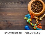 Stock photo large bowl of pet dog food with toys on wooden background top view mockup 706294159