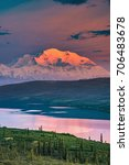 Small photo of alaska's mount denali looms behind wonder lake at colorful sunset with alpenglow