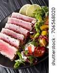 Small photo of Close up of rare seared Ahi tuna slices with fresh vegetable salad on a plate. vertical