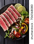 Small photo of Seared ahi tuna coated sesame seeds with salad on black plate closeup. Top view from above vertical