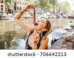 Stock photo young woman eating fresh harring standing outdoors in amsterdam city harring with onion is a 706642213