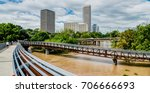 Panorama high and fast water rising in Bayou River from Rosemont pedestrian bridge with near town Houston in background, cloud blue sky. Heavy rains of Harvey Tropical Hurricane storm cause many flood