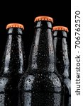 Water droplets on cold beer bottles with black background - stock photo