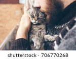 Stock photo close up of beard man in icelandic sweater who is holding and kissing his cute purring devon rex 706770268