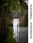 Small photo of Native American dream catcher made of a circular hoop with woven radial pattern net and hanging lace streamers, with blurry natural plant background