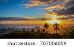 Small photo of Stunning sunset view of downtown Honolulu, Hawaii as seen from the iconic Tantalus Overlook lookout point with palm tree silhouettes in the sunlight, bright orange clouds, and the ocean horizon