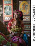 Small photo of Beautiful Tibetan costume,Tibetan mother and daughter,mother and daughter in room. mother and daughter have smile.