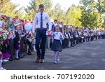 Small photo of Adygea, Russia - September 1, 2017: student the senior class and the girl a first-grader with a bell in her hand at school the solemn ruler in day of knowledge