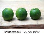 fresh organic limes on wooden... | Shutterstock . vector #707211040