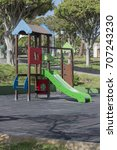 Small photo of Park game equipment for kids: green slide and ropes wall.