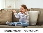 Small photo of childhood, emotions and people concept - happy smiling baby girl sitting on sofa and clapping hands at home