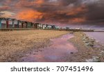 sunset over beach huts on a...