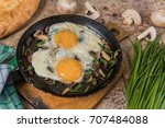 Small photo of Fried eggs with mushrooms and jusai (allium ramosum). Breakfast in azian style, top view.