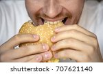 man eating hamburger with... | Shutterstock . vector #707621140